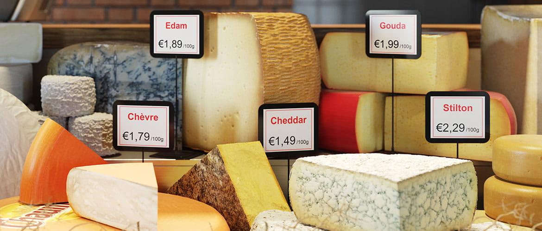 Theke mit Käsesorten und Namens- und Preisetiketten