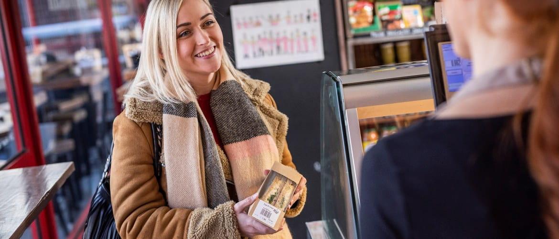 Frau kauft im Supermarkt ein Sandwich mit Barcode-Etikett
