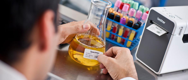 Labormitarbeiter beschriftet eine Probe mit einem Barcodeetikett aus dem Etikettendrucker.