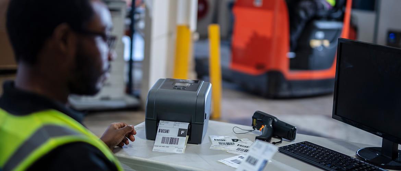 Lagerarbeiter druckt Versandlabels auf einem Etikettendrucker aus.