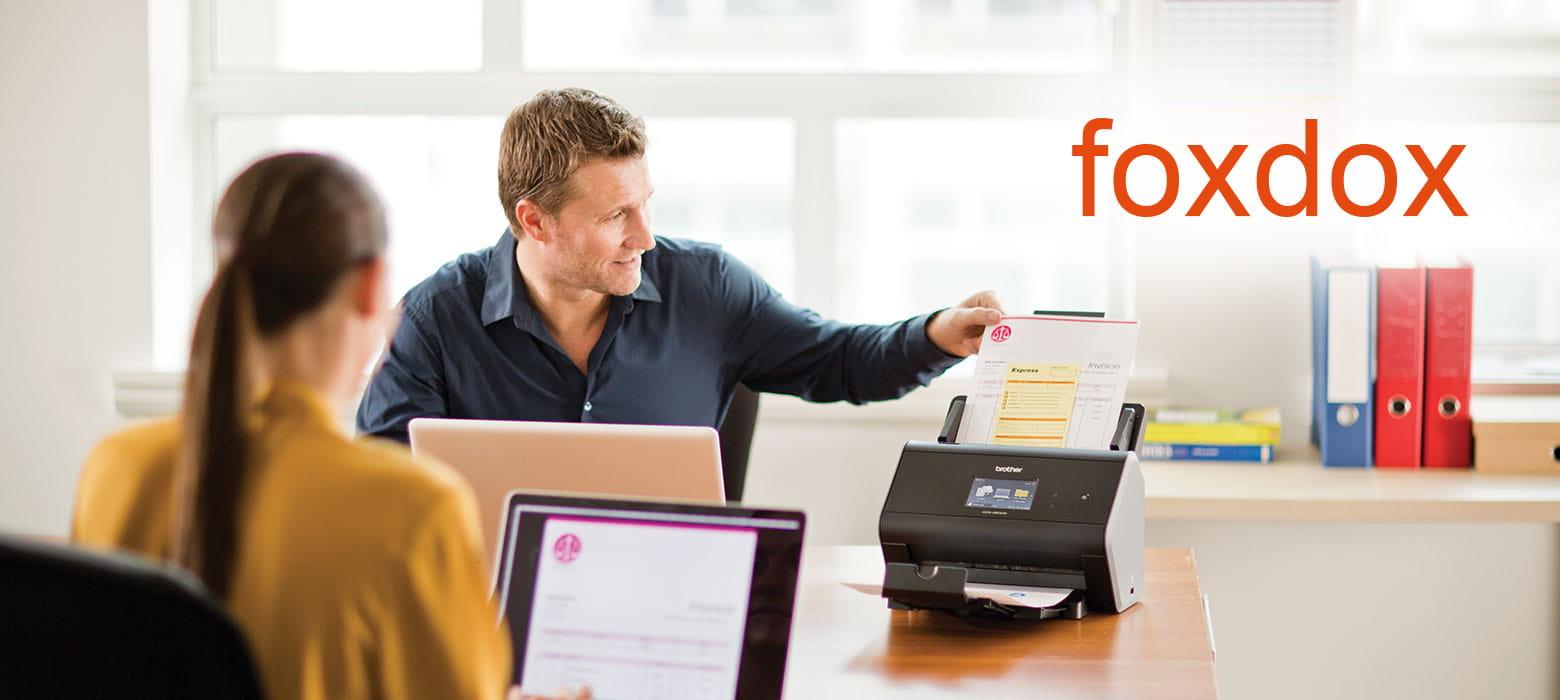 Mitarbeiter im Büro scannt Dokumente verschiedener Formate ein.