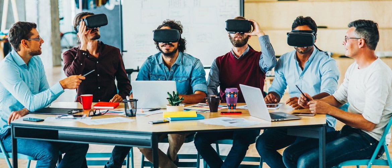Menschen sitzen mit VR-Brillen an Bürotisch