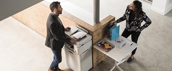Blick von oben auf eine Frau und einen Mann, die sich im Büro am Drucker unterhalten.