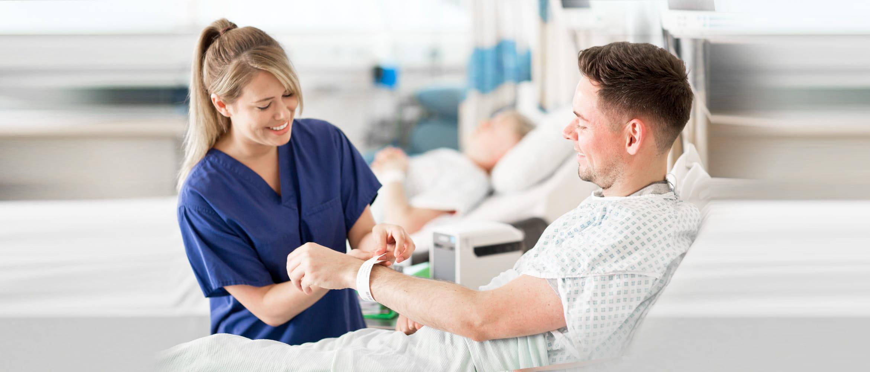 Krankenschwester legt Patient gedrucktes Armband um