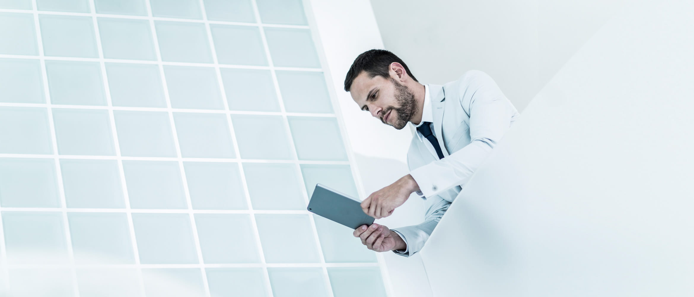 Mann in weißem Anzug lehnt an Glaswand in hellem, futuristischem Gebäude
