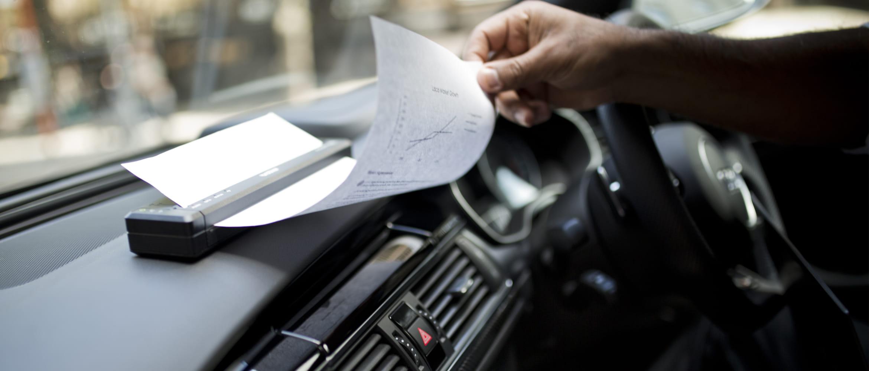 Versicherungsangestellter druckt auf mobilem Brother Drucker im Auto