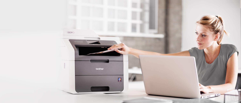Büromitarbeiterin sitzt an Laptop und druckt Dokument aus, Drucker steht auf dem Tisch