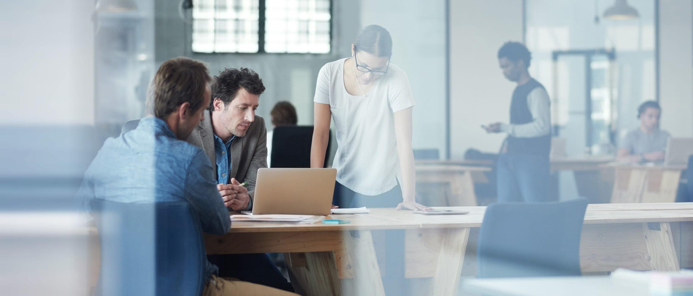 Kollegen besprechen Projekt am Laptop in Agenturumgebung