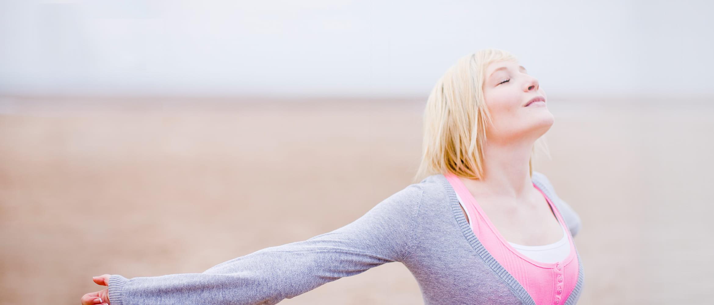 Frau geht Strand entlang, atmet tief durch und genießt den Moment