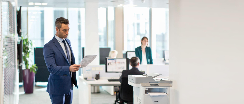 Büromitarbeiter schaut auf Ausdruck, vor Brother Drucker stehend, Office im Hintergrund