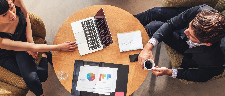 Mann und Frau disskutieren an Schreibtisch mit Laptop und Kaffee