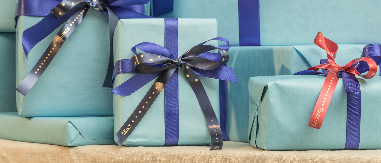 Geschenkboxen mit blauem Brother Textilband, goldene Schrift.