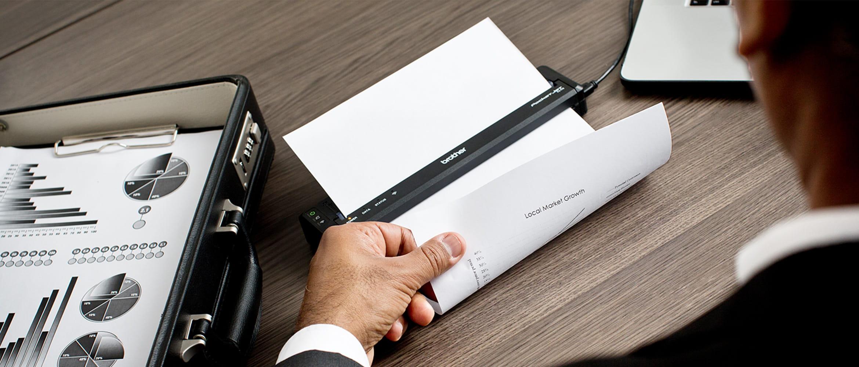 Mobile Brother Pocket Jet Drucker druckt Dokument, auf  dunklem Holztisch stehend, Person entnimmt Ausdruck