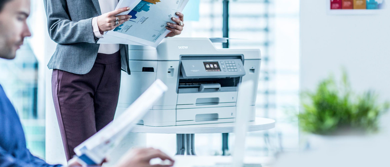 Brother Tintenstrahl-Multifunktionsdrucker in Büro Umgebung, Mitarbeiterin hält Ausdruck in der Hand