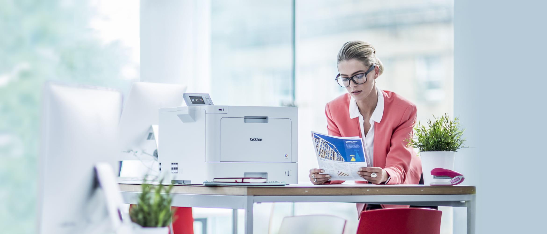 Agenturmitarbeiterin lehnt an Tisch und liest Dokument, Brother Farblaserdrucker auf dem Tisch stehend