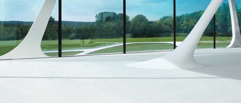 Futuristisches Gebäude mit Glasfassade, Wiesen und Wald im Hintergrund