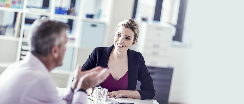 Frau und Mann inm Gespräch, lächelnd in Office-Umgebung, Brother Drucker im Hintergrund
