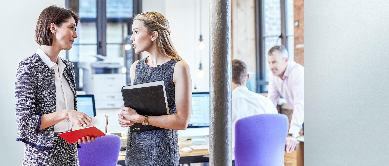Zwei Frauen im Gespräch in Büroumgebung, einen Ordner und Notizbuch haltend, weitere Personen im Hintergrund