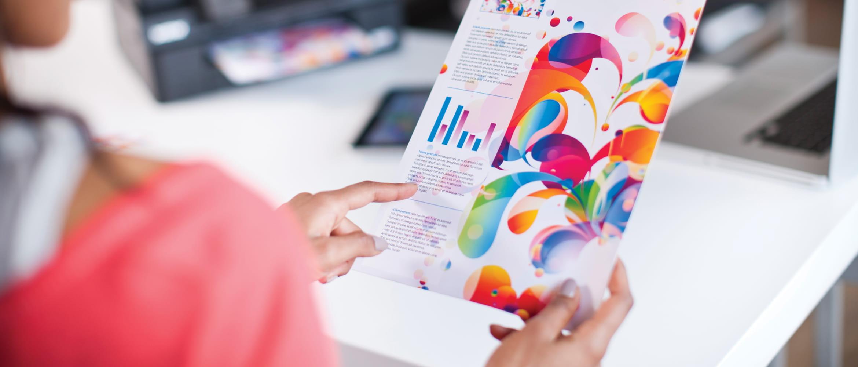 Frau hält farbigen Tintenstrahl-Ausdruck in der Hand, Brother Drucker im Hintergrund