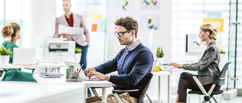 Vier Kollegen arbeiten im Office, unterhalten sich und schreiben E-Mails