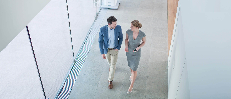Mann und Frau unterhalten sich während sie einen Flur entlanglaufen