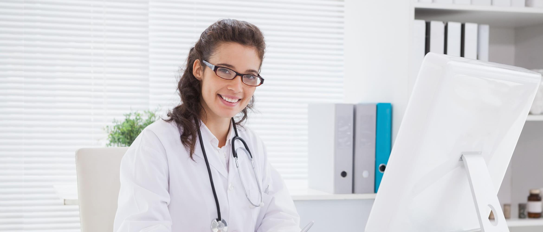 Ärztin am Schreibtisch sitzend, lächelt in die Kamera