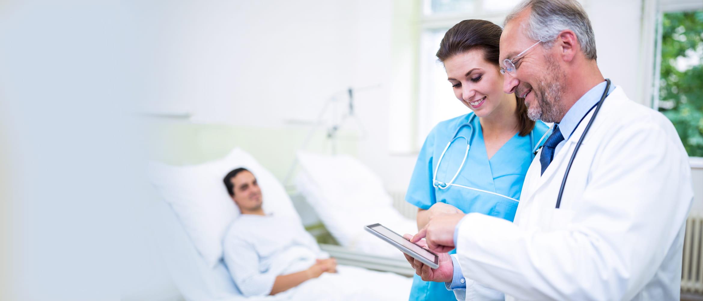 Arzt mit Krankenschwester im Gespräch, auf Patientenakte schauend, Patient im Hintergrund