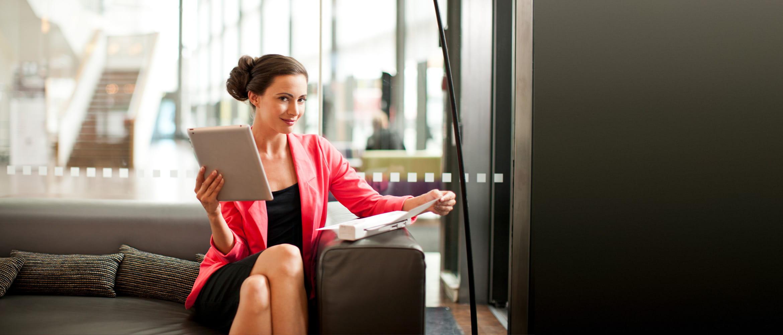 Geschäftsfrau bedient mobilen Brother Scanner, auf Couch sitzend, Tablet in der Hand haltend
