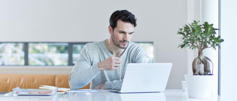 Mann sitzt an Schreibtisch und schaut in Laptop, Loftwohnung im Hintergrund