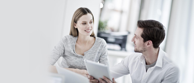 Mann und Frau in Office-Umgebung im Gespräch, Tablet in der Hand haltend