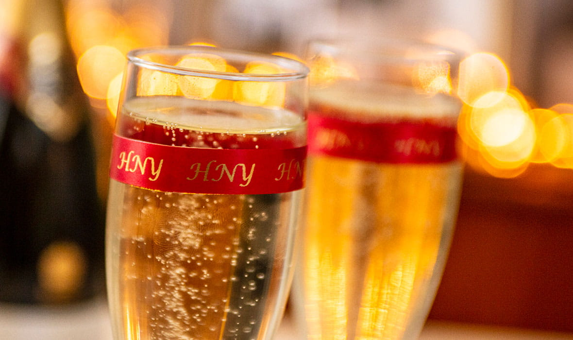 Zwei Champagnerflöten, umhüllt von einem Textilschriftband mit dem Text