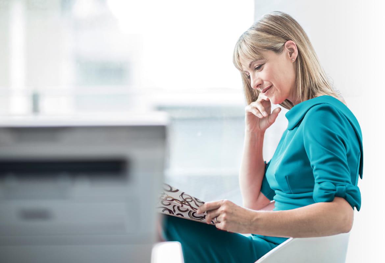 Frau liest Zeitung, Drucker im Hintergrund
