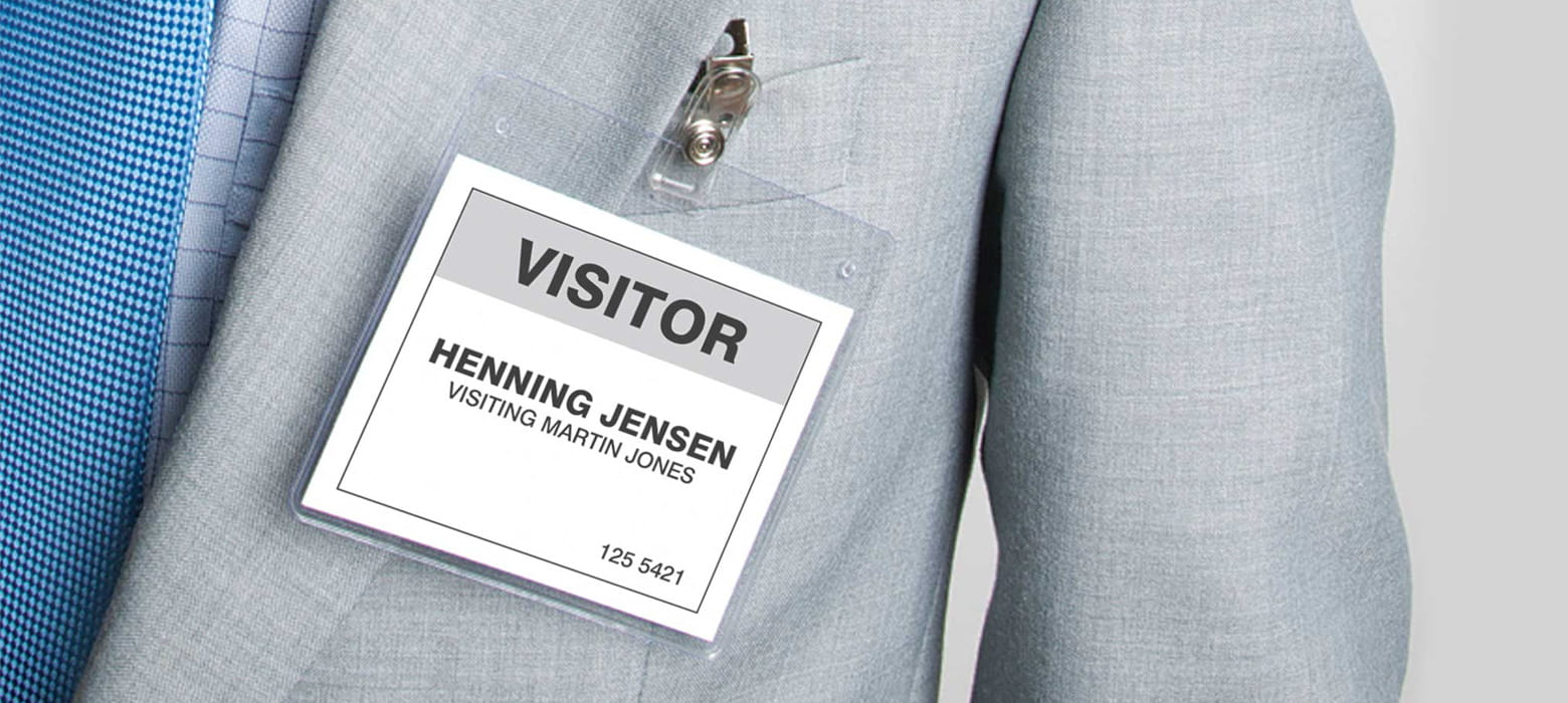 Mann im Anzug trägt einen Besucherausweis