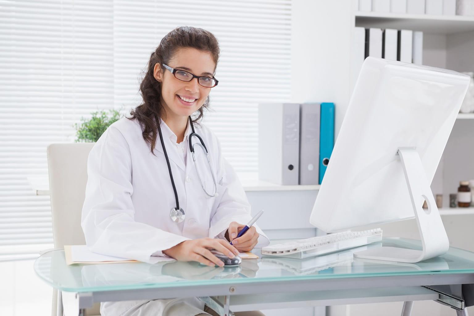 Ärztin sitzt an ihrem Schreibtisch