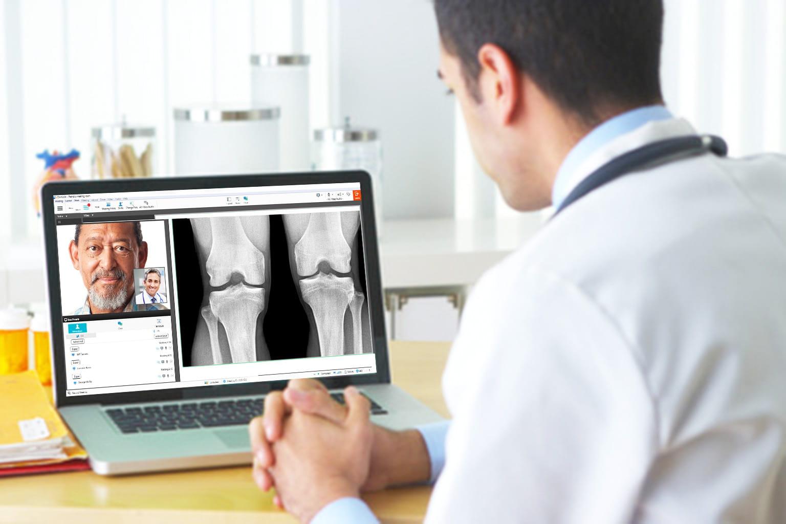 Arzt bespricht mit Patient Röntgenaufnahmen über Videokonferenz