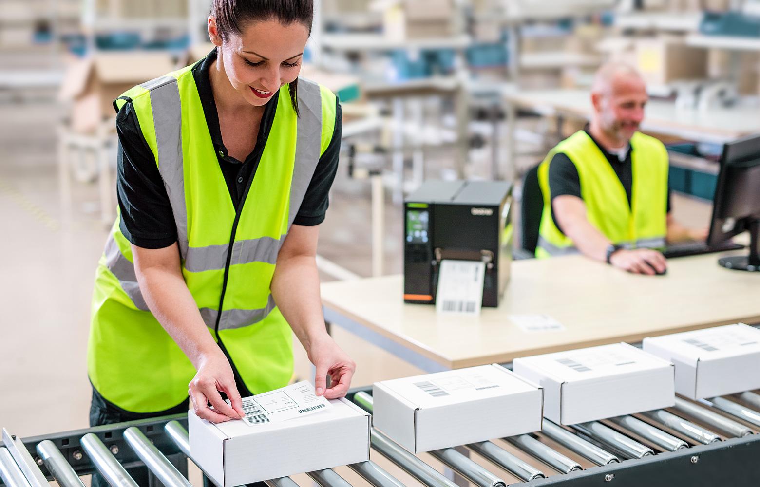 Frau in Warnweste klebt Etiketten auf Pakete, am Fließband stehend, TJ-Etikettebdrucker im Hintergrund auf Tisch
