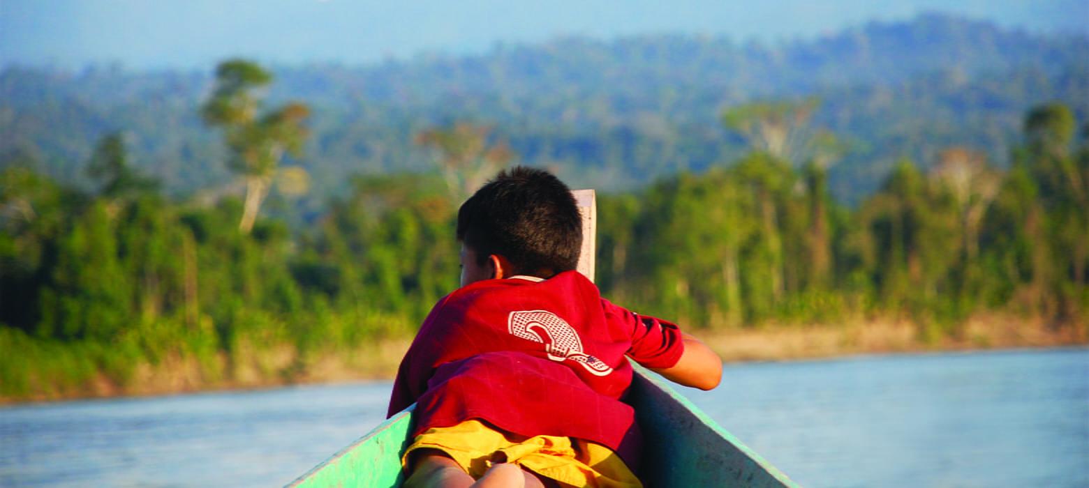 Kleiner Junge sitzt vorne im Boot und beobachtet Jungle und Fluss