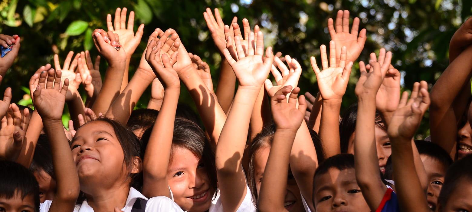 Jubelnde Kinder, die ihre Arme Richtung Himmel recken