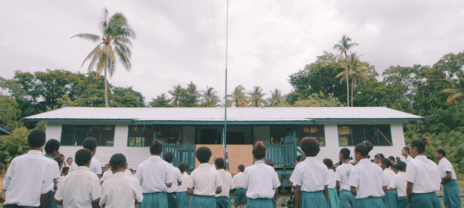 Schulkinder stehen vor ihrer Schule im Regenwald