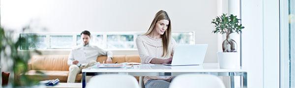 Frau sitzt an einem Schreibtisch, vor einem Laptop
